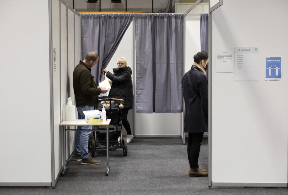 People vote at a local sports complex in Kopavogur, Iceland, Saturday, Sept. 25, 2021. Icelanders are voting in a general election dominated by climate change, with an unprecedented number of political parties likely to win parliamentary seats. (AP Photo/Arni Torfason)