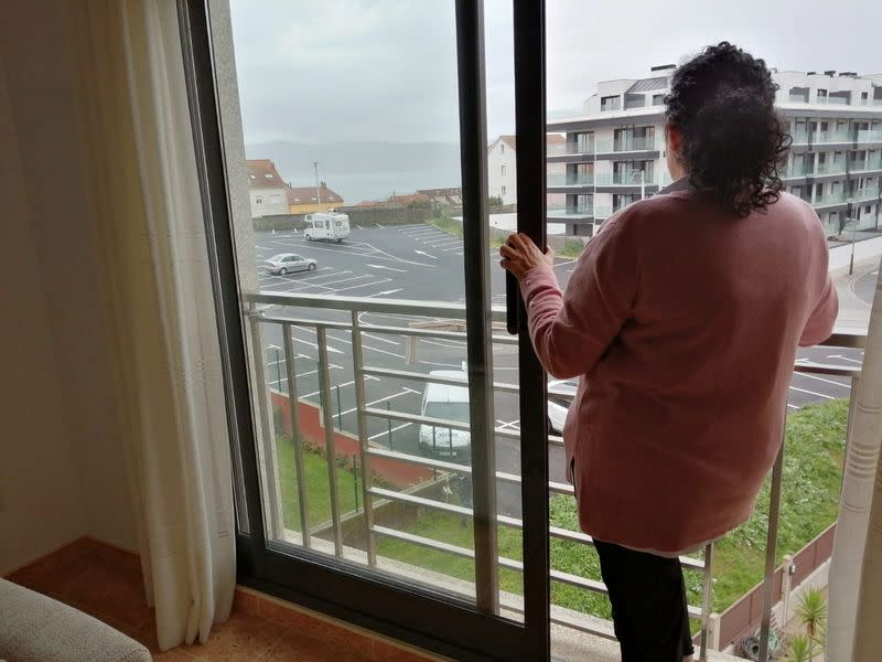 Airbnb host Perla Requejo stands at the window of the property that she rents to holidaymakers on Airbnb in Sanxenxo