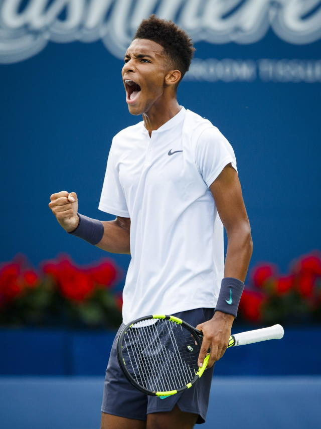Felix Auger-Aliassime, of Canada, celebrates winning a set against Lucas Pouille, of France, during the Rogers Cup men's tennis tournament in Toronto, Tuesday, Aug. 7, 2018. (Mark Blinch/The Canadian Press via AP)