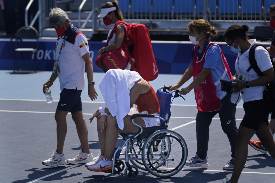 Paula Badosa, of Spain, is helped off the court in a wheelchair after retiring due to illness during the quarterfinals of the tennis competition at the 2020 Summer Olympics, Wednesday, July 28, 2021, in Tokyo, Japan. (AP Photo/Seth Wenig)