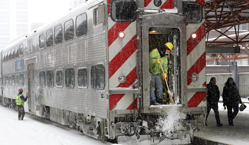 Commuters arrive at a snow-covered station (AP)
