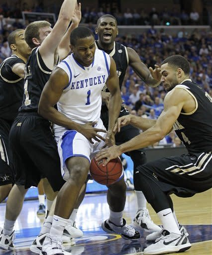 Kentucky guard Darius Miller (1) fights for a loose ball with Vanderbilt forward Jeffery Taylor (44) during the first half of an NCAA college basketball game in the championship game of the Southeastern Conference tournament at the New Orleans Arena in New Orleans, Sunday, March 11, 2012. (AP Photo/Bill Haber)