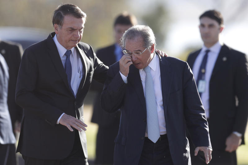 Brazil's President Jair Bolsonaro, left, talks with his Economy Minister Paulo Guedes as they arrive for the Brazilian flag-raising ceremony, in front of his official residence of the Alvorada Palace, in Brasilia, Brazil, Tuesday, Aug. 13, 2019. Brazilian students and teachers across Brazil are protesting budget cuts proposed by the Bolsonaro administration, in all major cities, including Sao Paulo, Rio de Janeiro and Brasilia. (AP Photo/Eraldo Peres)