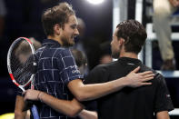 Daniil Medvedev of Russia, left, puts his arm around Dominic Thiem of Austria after he wins their singles final tennis match at the ATP World Finals tennis tournament at the O2 arena in London, Sunday, Nov. 22, 2020. (AP Photo/Frank Augstein)