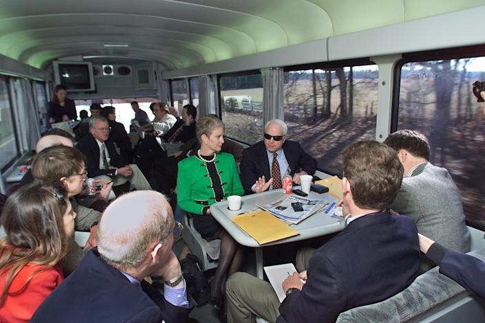 """Republican presidential hopeful Sen. John McCain, R-Ariz., and his wife, Cindy, speak with reporters as they travel from Columbia to Sumter, S.C., aboard the """"Straight Talk Express"""" on Jan. 7, 2000. (Photo: Paul J. Richards/AFP/Getty Images)"""