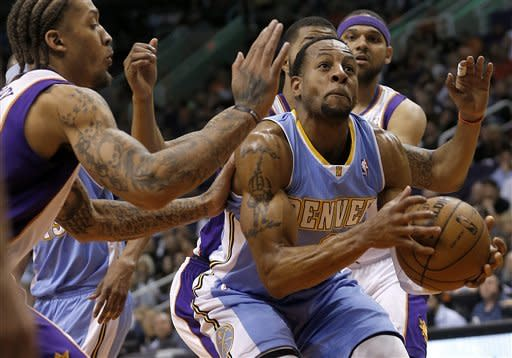 Denver Nuggets' Andre Iguodala tries to drive against Phoenix Suns' Michel Beasley, left, and Jared Dudley, right, during the first half of an NBA basketball game, Monday, March 11, 2013, in Phoenix. (AP Photo/Matt York)