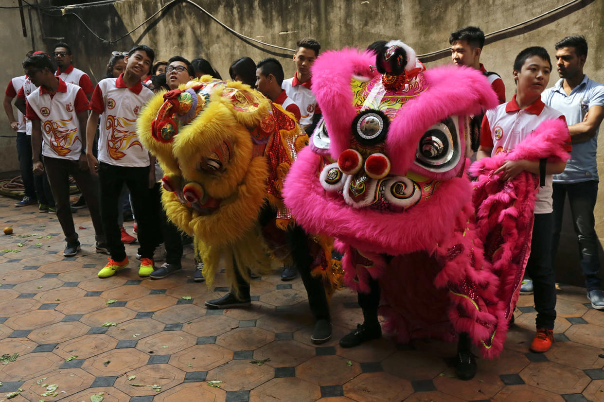 Indian ethnic Chinese boys wait to perform a lion dance on the first day of Chinese lunar new year in Kolkata, India, Saturday, Jan. 28, 2017. Chinese around the world are celebrating this year's Year of the Rooster according to the Chinese zodiac calendar. (AP Photo/Bikas Das)