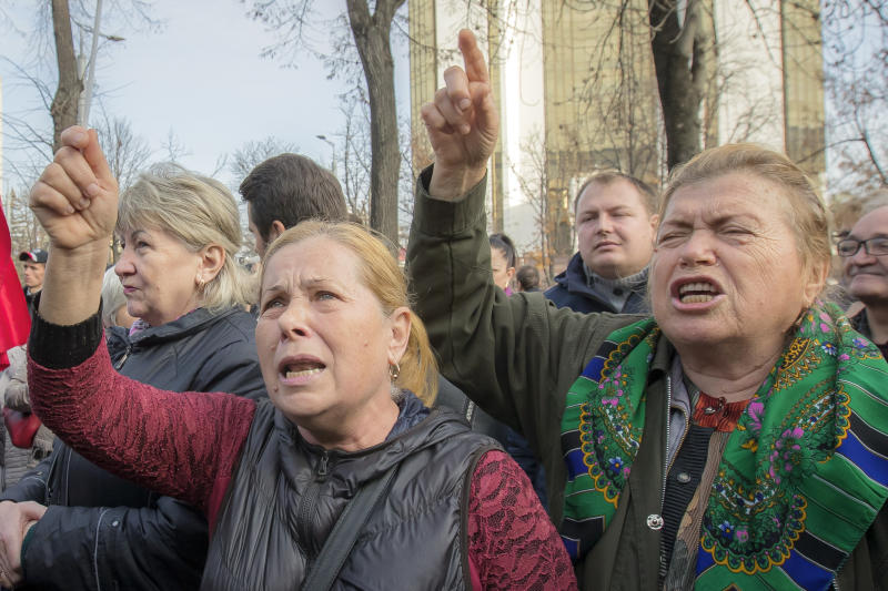 Supporters of the government shout slogans outside Moldova's parliament during a rally in Chisinau, Moldova, Tuesday, Nov. 12, 2019. Prime Minister Maia Sandu's government coalition between a pro-European group and a Russian-backed party has fallen after losing a no-confidence vote in parliament as 63 of 101 lawmakers supported the no-confidence motion.(AP Photo/Roveliu Buga)