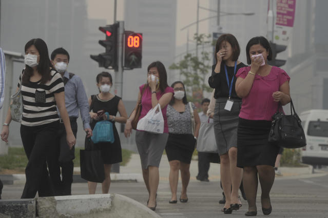 The office workers cover their mouths and noses while others wear masks as they cross a road on Thursday, June 20, 2013. Singapore urged people to remain indoors amid unprecedented levels of air pollution Thursday as a smoky haze wrought by forest fires in neighboring Indonesia worsened dramatically. (AP Photo/Joseph Nair)