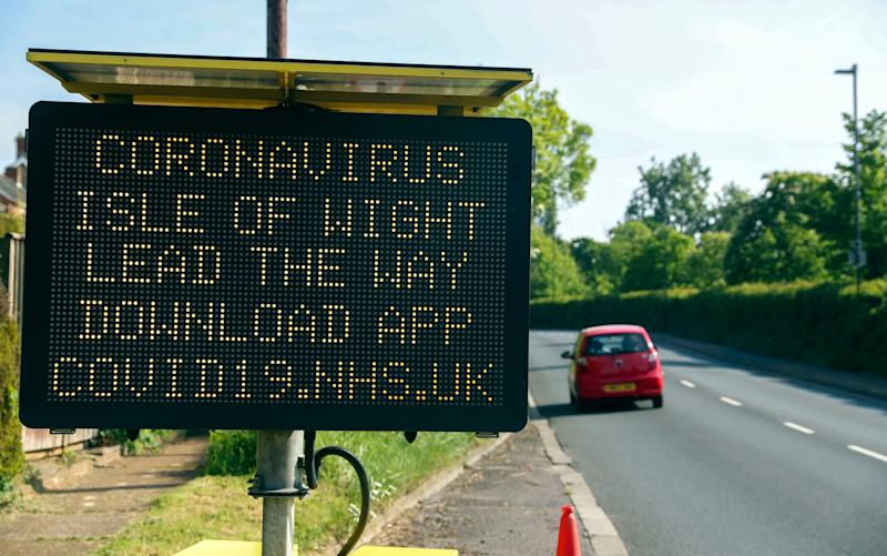 A sign telling people in the Isle of Wight to download the NHS coronavirus contact tracing app, which Isle of Wight residents have been getting their hands on, as the island plays the role of guinea pig to the technology which is hoped to enable at least a partial return to normal life - PA