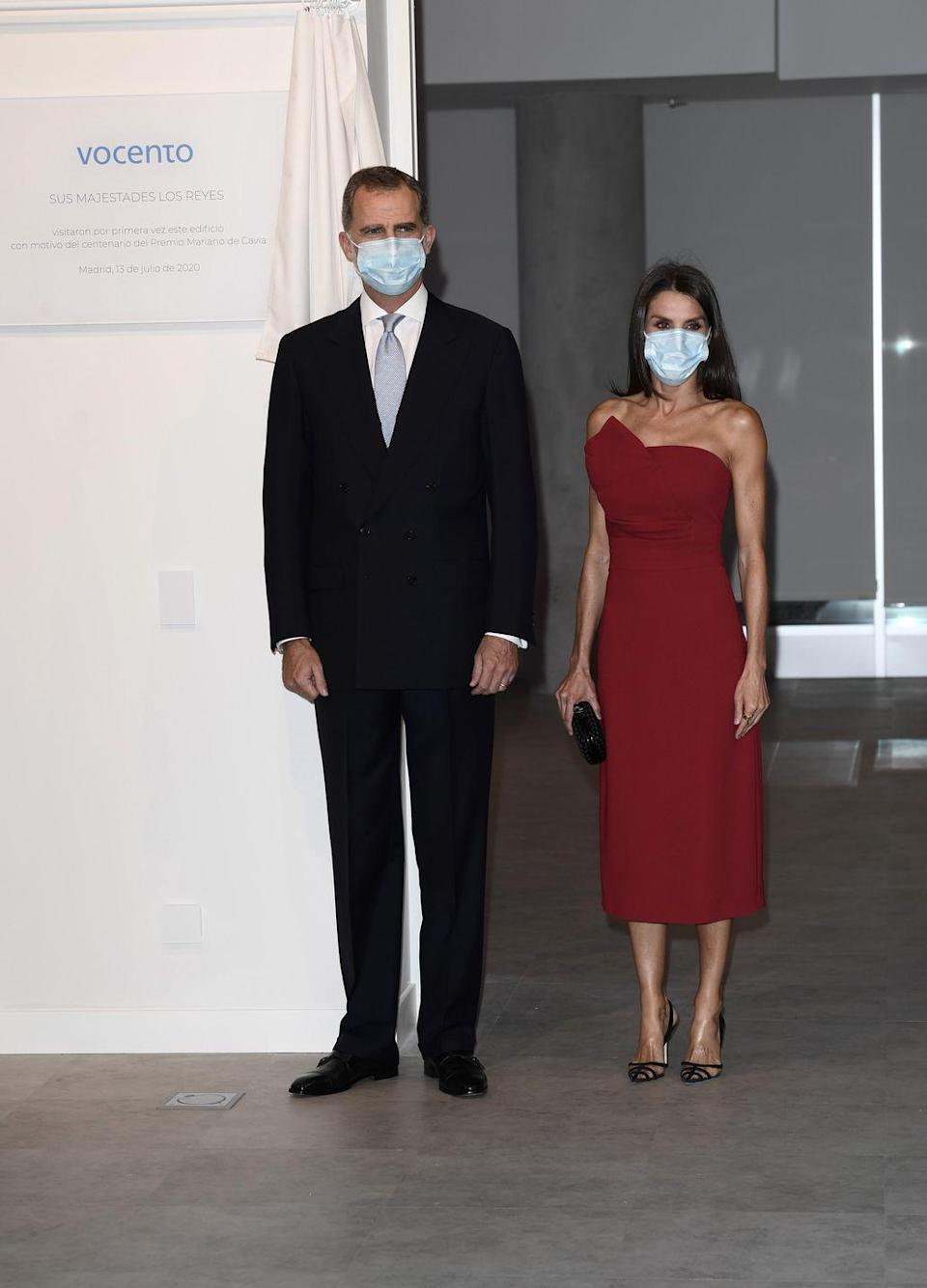 <p>Queen Letizia of Spain joins her husband King Felipe at a dinner in honor journalists. For the event she chose a rich red dress and accessorized with a small black clutch and a medical mask.</p>