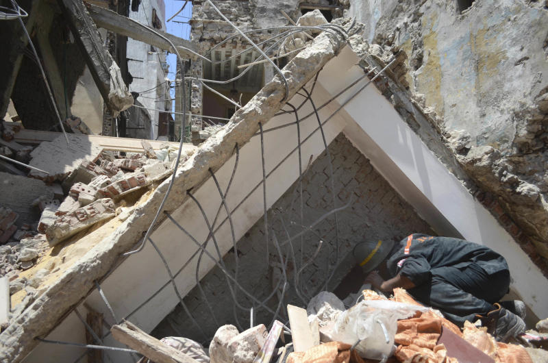 A rescue worker looks for survivors buried under debris of damaged buildings following the collapse of an 11-story building under construction onto three adjacent buildings that killed at least 10 people in the Gomrouk neighborhood of Alexandria, Egypt, July 15, 2012. With real estate at a premium in big cities like Alexandria and Cairo, developers seeking bigger profits frequently violate planning permits and exceed the number of stories allowed. (AP Photo/Tarek Fawzy)