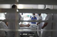 FILE- In this March, 19, 2021, file photo, medical staff meets in a room of a patient affected by COVID-19 virus in the ICU unit at the Ambroise Pare clinic in Neuilly-sur-Seine, near Paris. France's president say he has nothing to be sorry about for refusing to impose a third virus lockdown earlier this year, even though his country is now facing surging infections that are straining hospitals and more than 1,000 people with the virus are dying every week. (AP Photo/Thibault Camus, File)