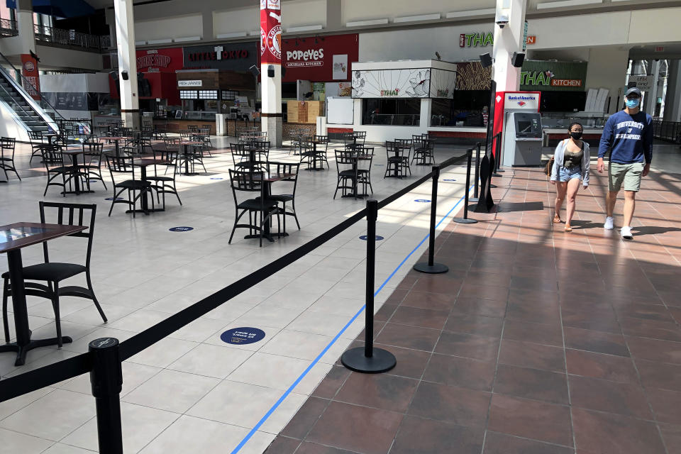 People walk past the nearly empty food court at Providence Place shopping mall, Monday, June 1, 2020, in Providence, R.I. Providence Place was opened Monday for the first time since mid-March when it was closed in response to the coronavirus crisis. The food court is open with adjusted seating to maintain social distancing. (AP Photo/Steven Senne)