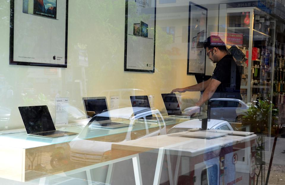 An indian salesman checks Apple Macbook laptops in an authorised Apple Store, in Allahabad on May 23,2016.An indian man works on his Apple macbook in his shop, in Allahabad on May 23,2016. Apple has announced that it will set up an app design and development center in southern India, shortly after company chief Tim Cook arrived in the country on his first visit. (Photo by Ritesh Shukla/NurPhoto via Getty Images)