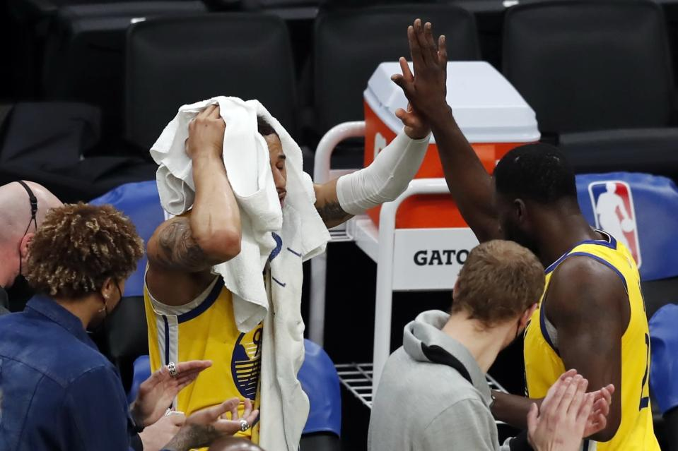 Golden State Warriors' Juan Toscano-Anderson, left, holds a towel to his head as he leaves an NBA basketball game after falling out of bounds during the second half against the Boston Celtics, Saturday, April 17, 2021, in Boston. (AP Photo/Michael Dwyer)