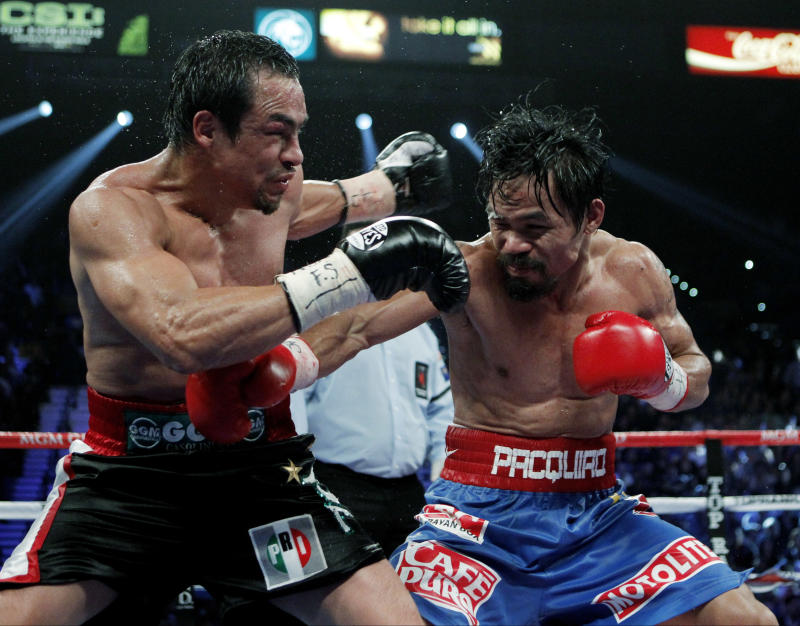 FILE - In this Nov. 12, 2011, file photo, Mexico's Juan Manuel Marquez, left, wearing the emblem of the opposition Institutional Revolutionary Party, PRI, on his boxer's trunks is hit by Manny Pacquiao, right, of the Philippines, during a WBO welterweight title fight in Las Vegas.  Mexico's highest electoral court says it has overturned a recent municipal election partly because of a strange new form of political advertising _ a party logo emblazoned on a boxer's trunks. (AP Photo/Jae C. Hong, file)