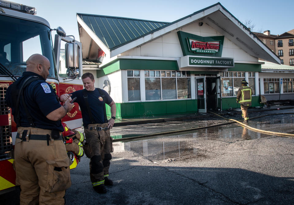 Firefighters talk in front of a burned Krispy Kreme Doughnuts store in Atlanta on Wednesday, Feb. 10, 2021. The historic store was engulfed in flames early Wednesday. The store owned by Basketball Hall-of-Famer Shaquille O'Neal was significantly damaged. (AP Photo/Ron Harris)