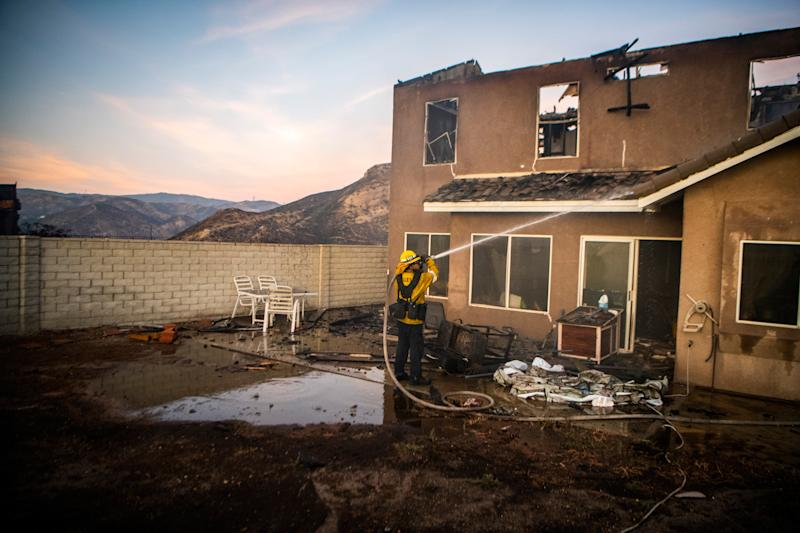 A firefighter hoses down a damaged house as the Tick Fire burns in the Santa Clarita, Calif., area on Oct. 24, 2019.   Stuart W. Palley
