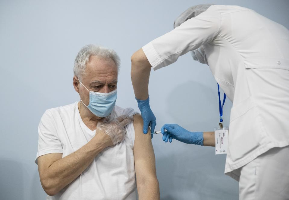 FILE - In this Jan. 20, 2021, file photo, a Russian medical worker, right, administers a shot of Russia's Sputnik V coronavirus vaccine to a patient in a vaccination center in Moscow, Russia. Russia's boast in August that it was the first country to authorize a coronavirus vaccine led to skepticism because of its insufficient testing on only a few dozen people. Now, with demand growing for the Sputnik V, experts are raising questions again, this time over whether Moscow can keep up with all the orders from countries that want it. (AP Photo/Pavel Golovkin, File)