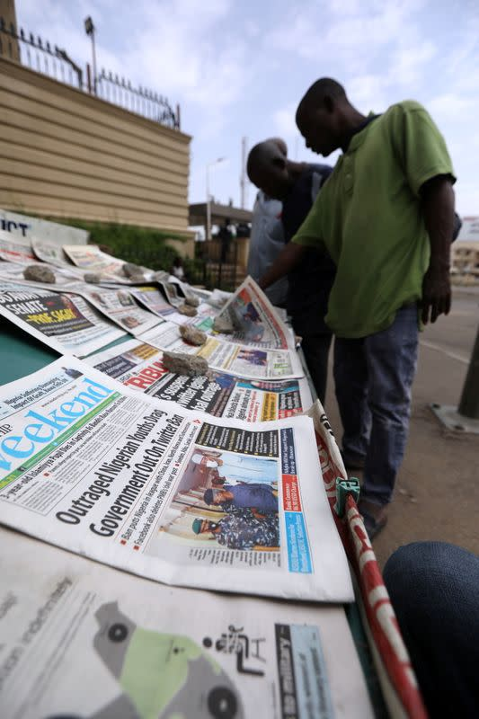 Pedestrians look at newspapers in Abuja