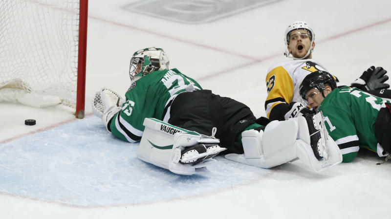 Dallas Stars goaltender Anton Khudobin (35), defenseman Ben Lovejoy (21) and Pittsburgh Penguins center Teddy Blueger (53) fall on the ice as the puck slides into the net during the second period of an NHL hockey game in Dallas, Saturday, March 23, 2019. The goal was waved off for goaltender interference by the Penquins. (AP Photo/LM Otero)