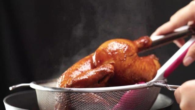 Removing cooked braised soy sauce chicken from pot
