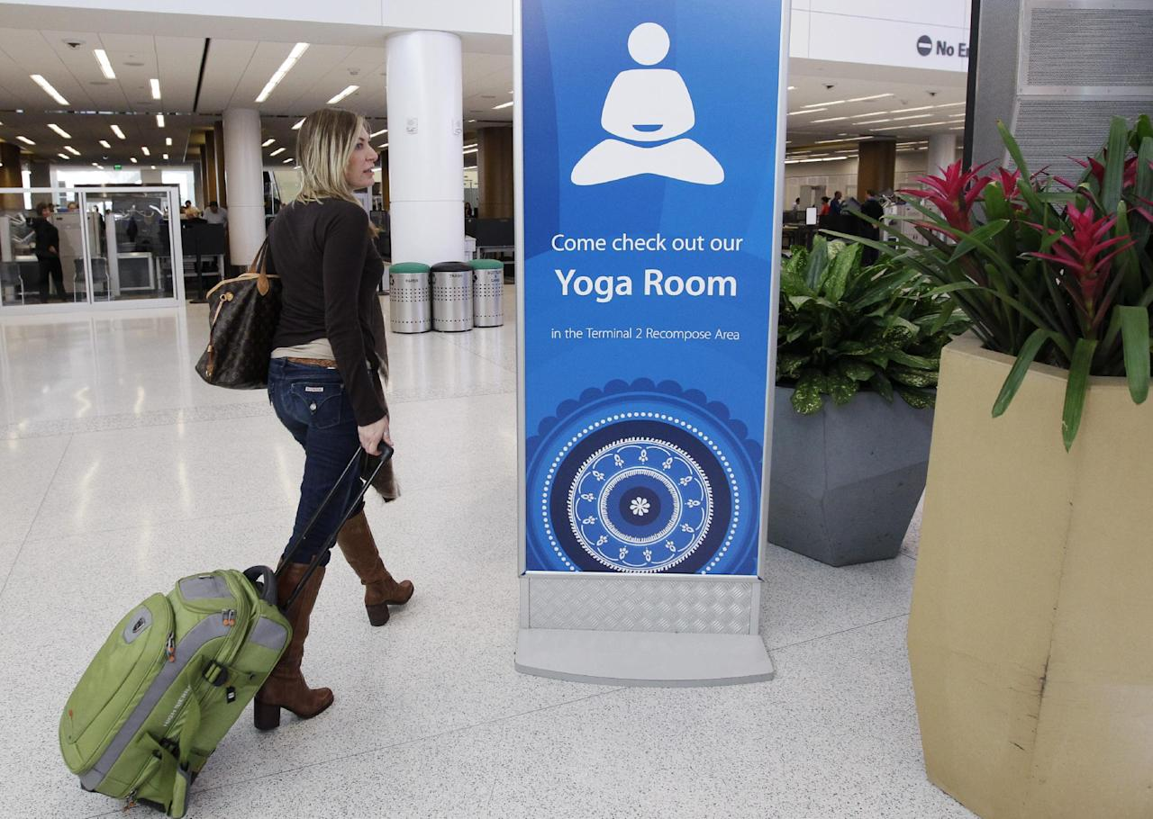 In this Friday, Jan. 27, 2012 photo, traveler Maria Poole leaves San Francisco International Airport's new Yoga Room after practicing in San Francisco. The quiet, dimly lit studio officially opened last week in a former storage room just past the security checkpoint at SFO's Terminal 2. Airport officials believe the 150-square-foot room with mirrored walls is the world's first airport yoga studio, said spokesman Mike McCarron. (AP Photo/Paul Sakuma)