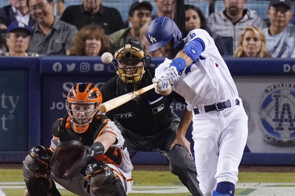 Los Angeles Dodgers' Chris Taylor, right, hits a two-run home run while San Francisco Giants catcher Buster Posey, left, and home plate umpire Dan Iassogna watch during the sixth inning of a baseball game Tuesday, July 20, 2021, in Los Angeles. (AP Photo/Mark J. Terrill)