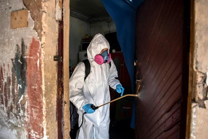 A municipal worker sanitizes the home of Haitian migrants in Santiago, amid mandatory total quarantine due to COVID-19 (AFP Photo/Martin BERNETTI)