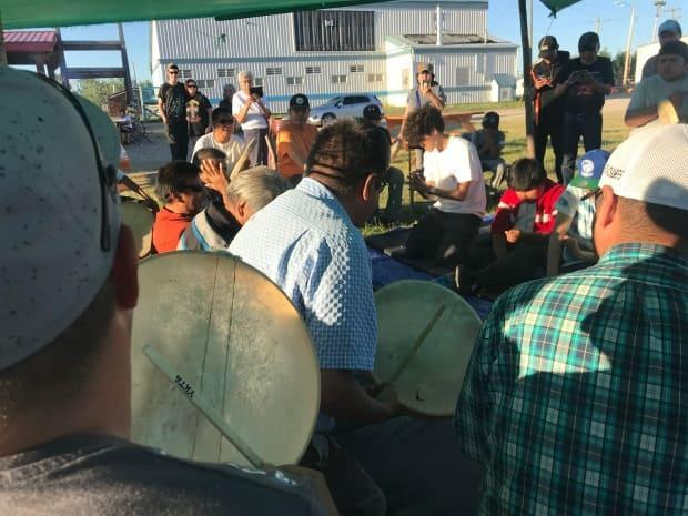 Men pound the drums and play Dene hand games at the 100-year commemoration of Treaty 11 in Fort Providence, N.W.T. (Anna Desmarais/CBC  - image credit)