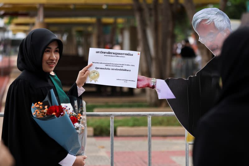 A student stands next to a cardboard figure of Somsak Jeamteerasakul, an exiled Thai academic, before a graduation ceremony, which some students have boycotted because it is led by King Maha Vajiralongkorn, at Thammasat University in Bangkok