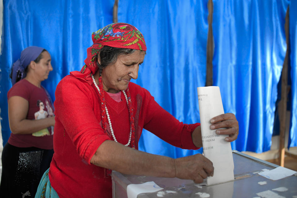 A woman casts her vote in Sintesti, Romania, Sunday, Nov. 10, 2019. Romania held a presidential election Sunday after a lackluster campaign that has been overshadowed by the country's political crisis, which saw a minority government installed just a few days ago.(AP Photo/Andreea Alexandru)