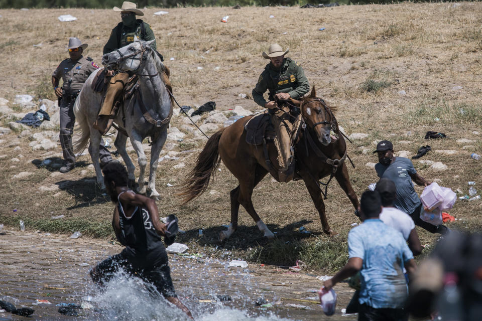 U.S. Customs and Border Protection mounted officers attempt to contain migrants trying to cross the Rio Grande river from Ciudad Acuna, Mexico, into Del Rio, Texas, Sunday, Sept. 19, 2021. (AP Photo/Felix Marquez)