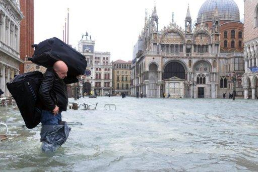 <p>A man carries luggages on a flooded St Mark's Square as floodwaters drenched most of the tourist destination of Venice and led to the evacuation of 200 people in Tuscany.</p>