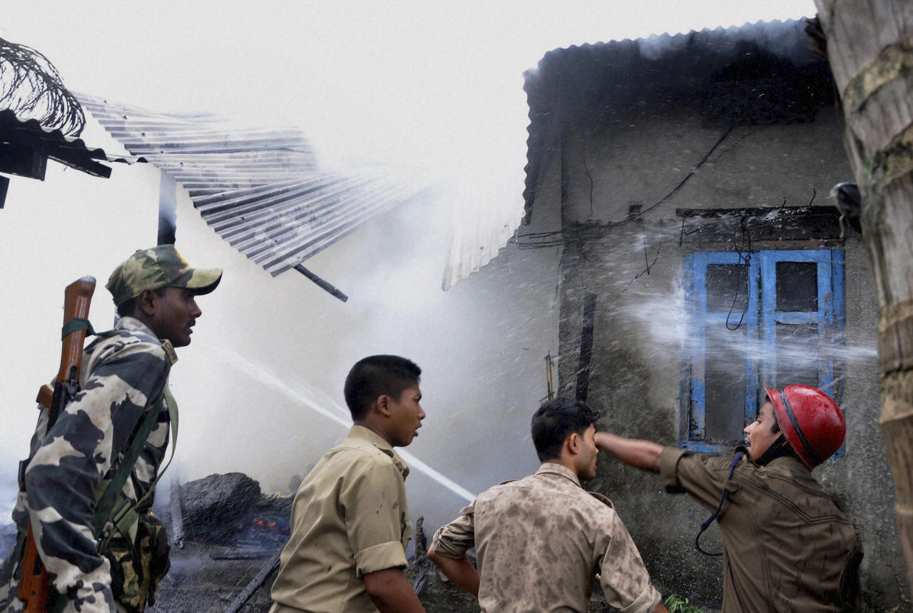 Indian fire fighters try to extinguish fire at a house following ethnic clashes in Kokrajhar, Assam state, India, Tuesday, July 24, 2012. Government troops sent to quell communal clashes over land rights in this northeast Indian state were under orders Tuesday to shoot suspected rioters on sight after some 21 people were killed in machete attacks and dozens of homes were burned to the ground. (AP Photo) INDIA OUT