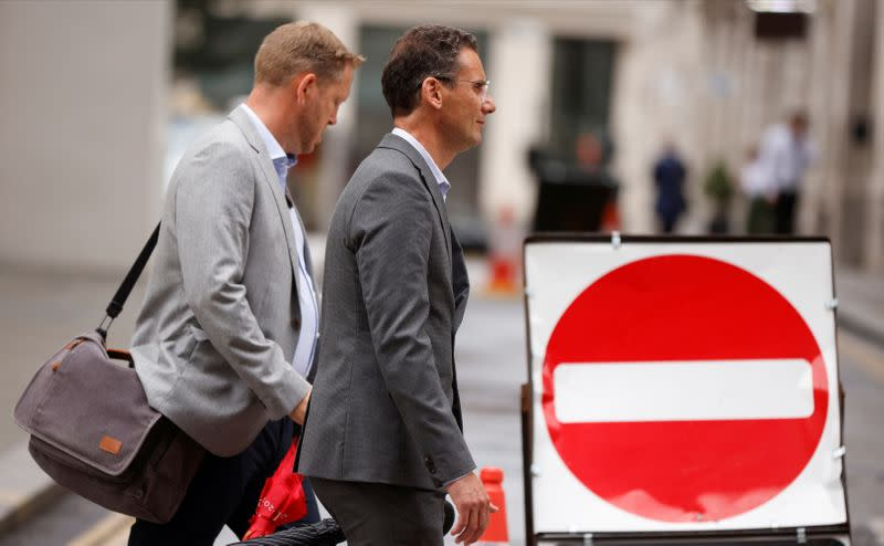 FILE PHOTO: People walk past a no entry sign in the City of London financial district amid the outbreak of the coronavirus disease (COVID-19)