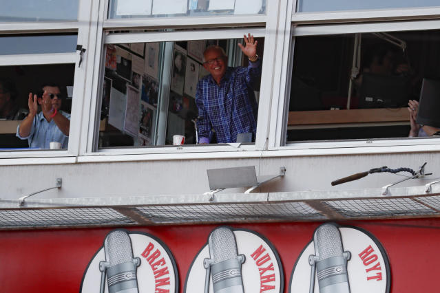 Cincinnati Reds announcer Marty Brennaman, center, waves to the crowd after the close of the fourth inning of a baseball game against the Milwaukee Brewers, Thursday, Sept. 26, 2019, in Cincinnati. (AP Photo/John Minchillo)
