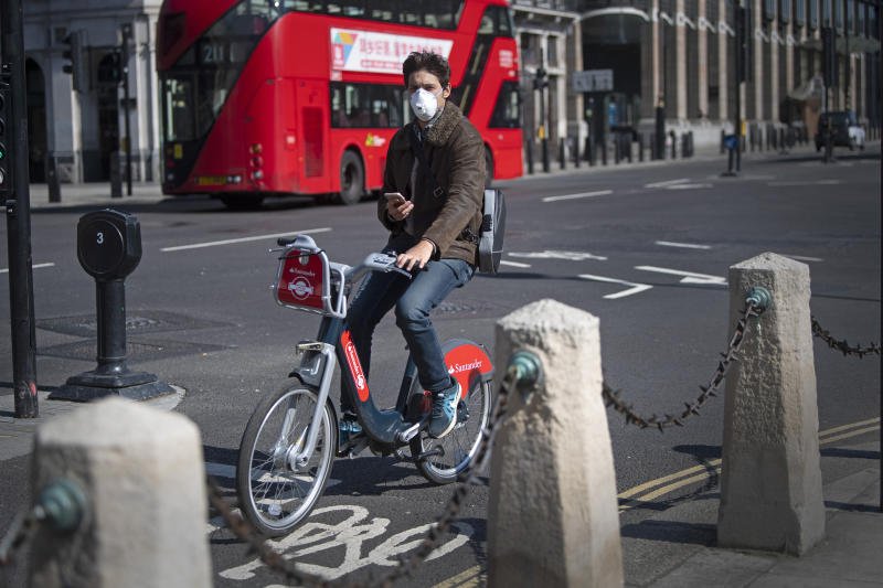 A man wearing a protective face mask cycles in Parliament Square in central London, after Prime Minister Boris Johnson has put the UK in lockdown to help curb the spread of the coronavirus.