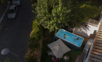 "Two young girls play in a portable plastic pool in the garden of a home in Seville, on Aug. 5, 2020. The owner Barbara Larraneta bought it ""like a lot of people in this city because of the heat, the covid and the lack of certainty about the summer and the restrictions"". As pretty much everywhere else, the coronavirus pandemic has meant more time at home for Spaniards. For many, of those furloughed or out of business it has also meant less income and no ways to afford a holiday to escape the sweltering temperatures of the Spanish summer. Searching for a solution to keep cool, portable pools have become the newest fad, taking over backyards, terraces, communal patios and even the streets of hot spots like Seville, in the country's south. (AP Photo/Laura Leon)"