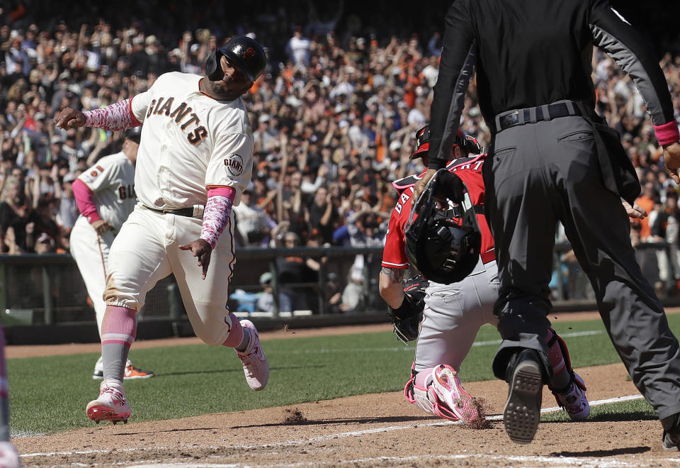 San Francisco Giants' Pablo Sandoval, left, runs home to score a run past Cincinnati Reds catcher Tucker Barnhart, bottom right, during the eighth inning of a baseball game in San Francisco, Sunday, May 12, 2019. (AP Photo/Jeff Chiu)