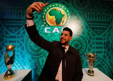 Soccer Football - African Champions League Group Stage Draw - Nile Ritz-Carlton Hotel, Cairo, Egypt - December 28, 2018 A member of the media takes a selfie with the CAF Champions League and the CAF Confederation Cup trophies on display before the draw REUTERS/Amr Abdallah Dalsh