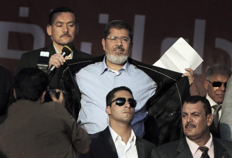 FILE - In this Friday, June 29, 2012 file photo, Egypt's President-elect Mohammed Morsi opens his suit jacket to show his supporters that he is not wearing body armor at Tahrir Square, the focal point of Egyptian uprising, during his speech in Cairo, Egypt. The message is clear: Morsi has nothing to fear because he sees himself as the legitimate representative of Egypt's uprising. His speeches reveal a populist bent, making generous promises that many are skeptical he can keep. And though he began as an awkward and uninspiring speaker, he appears to be striving to reinvent his decidedly uncharismatic public persona. (AP Photo/Amr Nabil, File)