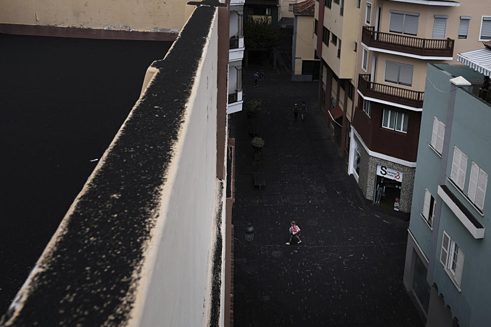 A woman walks down the street covered in ash from the volcano in Santa Cruz de la Palma on the Canary island of La Palma, Spain on Sunday Sept. 26, 2021. A massive cloud of ash prevented flights in and out of the Spanish island of La Palma on Sunday as molten rock continued to be flung high into the air from an erupting volcano. (AP Photo/Daniel Roca)