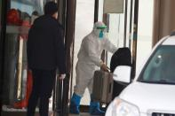 WHO team members tasked with investigating the origins of the coronavirus disease (COVID-19) pandemic leave their quarantine hotel in Wuhan