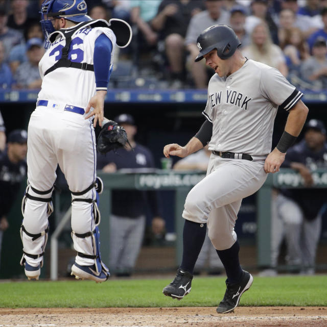 New York Yankees' Austin Romine, right, runs past Kansas City Royals catcher Cam Gallagher to score on a two-run double hit by Cameron Maybin during the second inning of the second baseball game in a doubleheader Saturday, May 25, 2019, in Kansas City, Mo. (AP Photo/Charlie Riedel)
