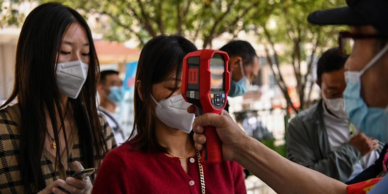 Passengers are given temperature checks before boarding a train in Wuhan, China, on May 12, 2020.