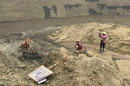Jade miners take photos at the mud pond where more than 50 people were killed in collapse, in Hpakant, Kachin, Myanmar April 28, 2019. REUTERS/Shoon Naing