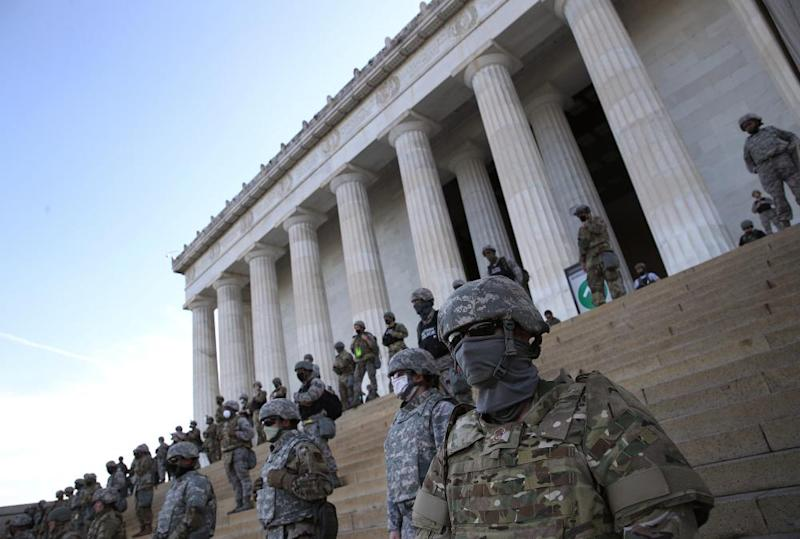 The DC national guard stand on the steps of the Lincoln Memorial as demonstrators participate in a peaceful protest.
