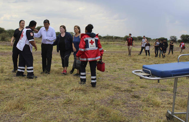 <p>In this photo released by Red Cross Durango communications office, Red Cross workers attend airline passengers who survived a plane crash, as they walk away from the crash site in a field near the airport in Durango, Mexico, Tuesday, July 31, 2018. (Photo: Red Cross Durango via AP) </p>